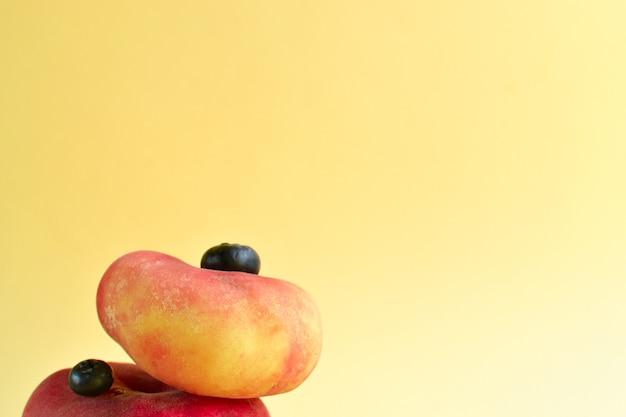 Pêssego em um fundo amarelo. pêssego e mirtilo maduros suculentos. conceito de comida criativa minimalista.