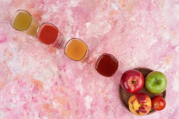Pêssego, limão e maçãs com copos de suco na placa de madeira.