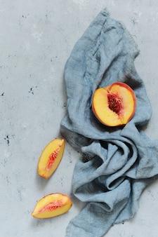 Pêssego maduro sobre um fundo cinza (azul). fruta suculenta do verão, copie o espaço.