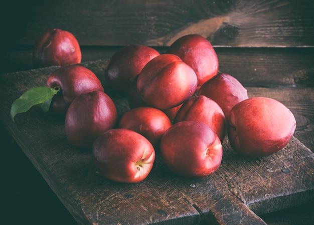 Pêssego maduro vermelho nectarina em uma placa de madeira marrom