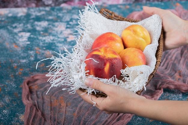 Pêssegos amarelos avermelhados em um pedaço de serapilheira branca.