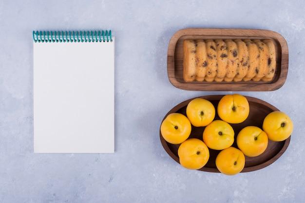 Pêssegos amarelos e bolo em bandejas de madeira com um caderno de lado