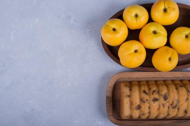 Pêssegos amarelos e bolo em bandejas de madeira no espaço azul