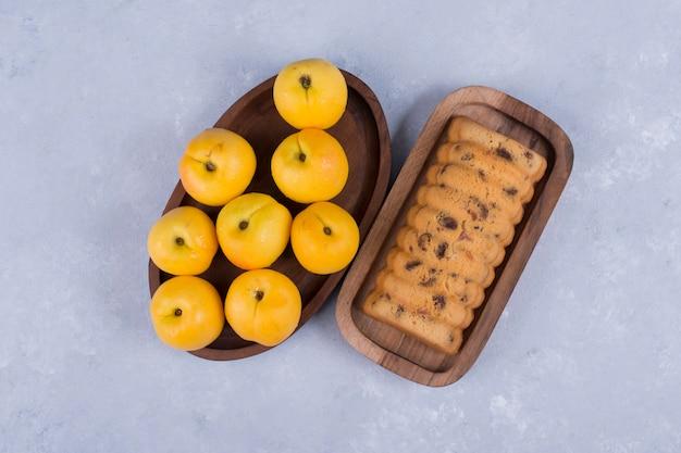 Pêssegos amarelos e rollcake em travessas de madeira no meio da mesa