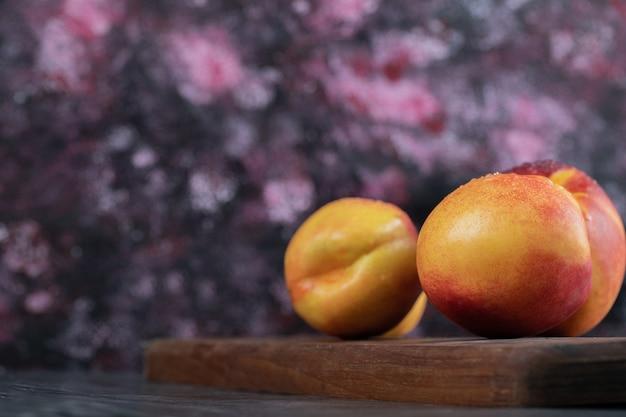 Pêssegos amarelos e vermelhos isolados em uma bandeja de madeira