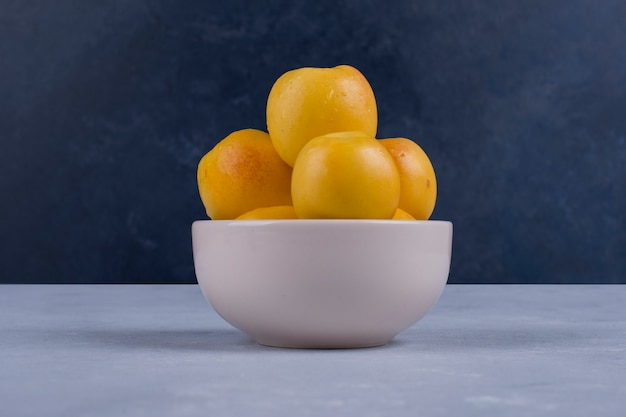 Pêssegos amarelos em uma tigela de cerâmica branca isolada no azul