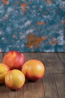 Pêssegos avermelhados isolados na mesa de madeira.