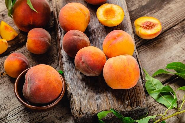 Pêssegos com folhas na mesa de madeira com pêssego ao meio. pêssegos maduros e suculentos. colheita de pêssegos para comida ou suco. frutas orgânicas frescas.