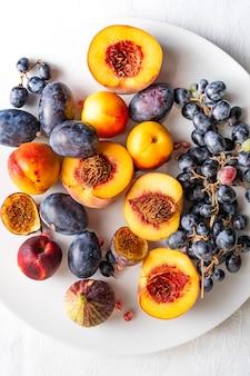 Pêssegos cortados ao meio com nectarinas e uvas na chapa branca