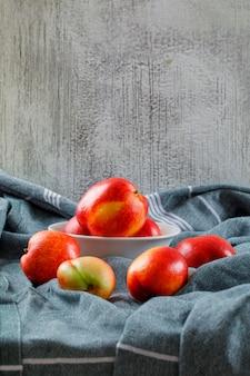 Pêssegos deliciosos em uma tigela vista lateral branca em uma textura de roupas e parede suja