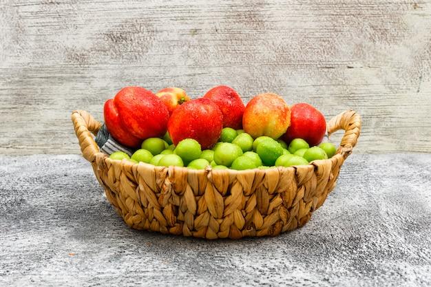 Pêssegos e greengages em uma cesta de vime e em um pano de piquenique na parede suja, cinza do grunge, vista lateral.