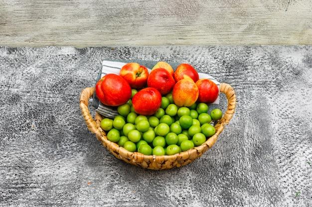 Pêssegos e greengages em uma cesta de vime e em um pano de piquenique no cinza e na madeira do grunge, opinião de ângulo alto.