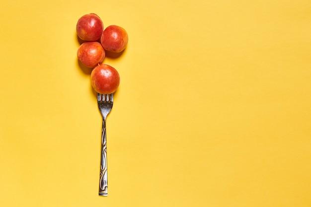 Pêssegos e um garfo em um fundo amarelo