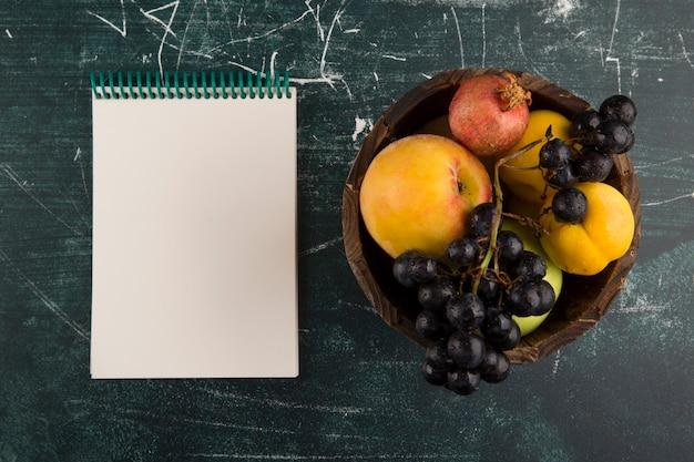 Pêssegos e uvas em uma tigela de madeira com um caderno de lado