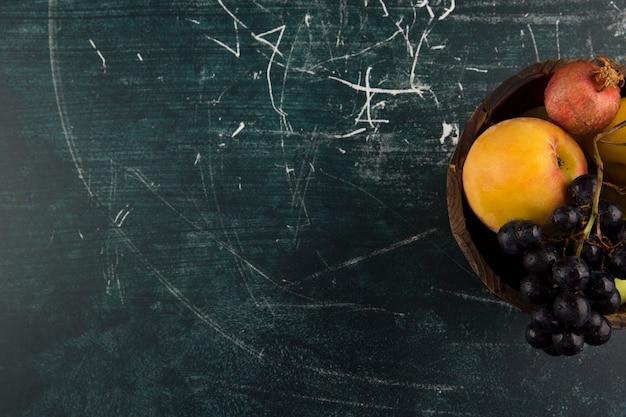 Pêssegos e uvas em uma tigela de madeira no quadro negro