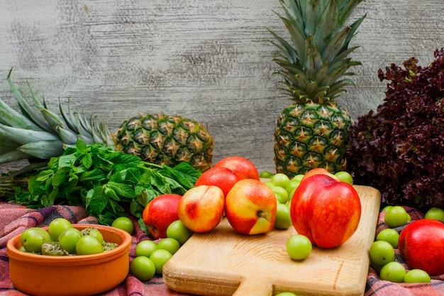 Pêssegos em uma placa de corte e tigela de barro com folhas verdes, dois abacaxis e alface vista lateral na parede de pano e grunge de piquenique
