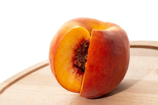Pêssegos em uma placa de madeira. pêssego ao meio com uma pedra. frutas maduras e suculentas