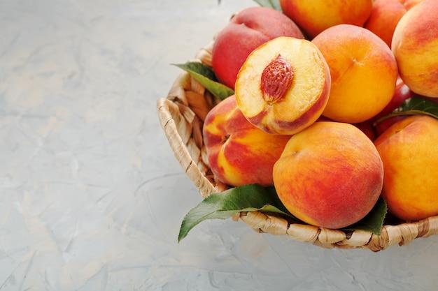 Pêssegos maduros em uma cesta de vime em uma mesa de pedra cinza com uma fatia de pêssego suculenta com um caroço de pedra.