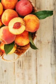 Pêssegos maduros frescos em uma cesta de vime