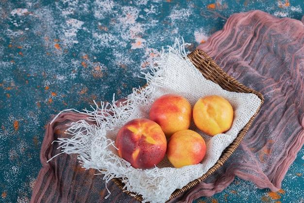 Pêssegos vermelhos amarelos na cesta de madeira em um pedaço de serapilheira branca.