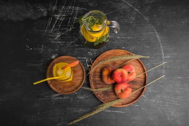 Pêssegos vermelhos com um copo de suco e limonada na jarra, vista de cima