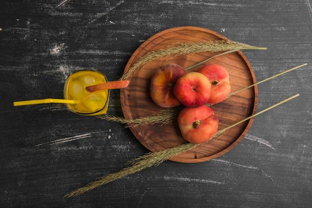 Pêssegos vermelhos com um copo de suco em uma travessa de madeira, vista de cima
