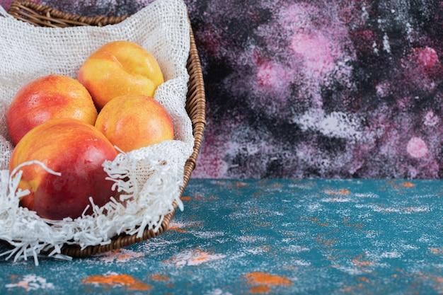Pêssegos vermelhos e amarelos em um pedaço de serapilheira branca.