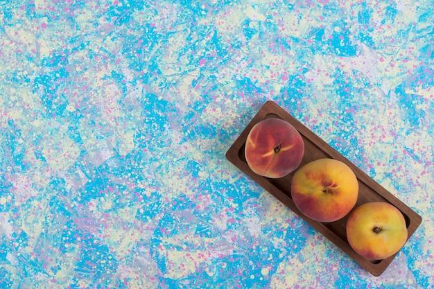 Pêssegos vermelhos e amarelos em uma bandeja de madeira sobre fundo azul no canto