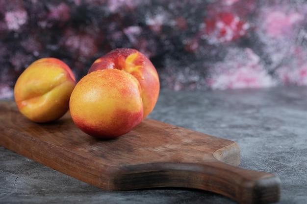 Pêssegos vermelhos e amarelos na placa de madeira na mesa.