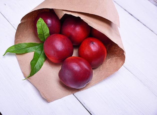 Pêssegos vermelhos maduros em um saco de papel