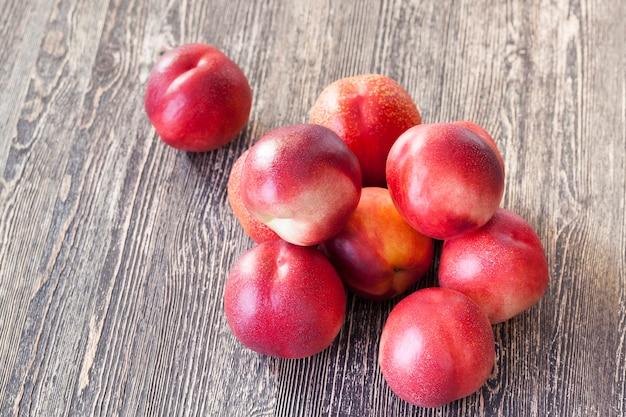 Pêssegos vermelhos maduros em uma mesa de madeira preta, cozinhando
