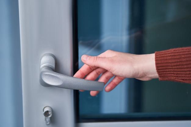 Pessoa abre a porta. mão na maçaneta da porta