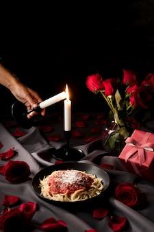 Pessoa acendendo uma vela para o jantar do dia dos namorados com macarrão e rosas