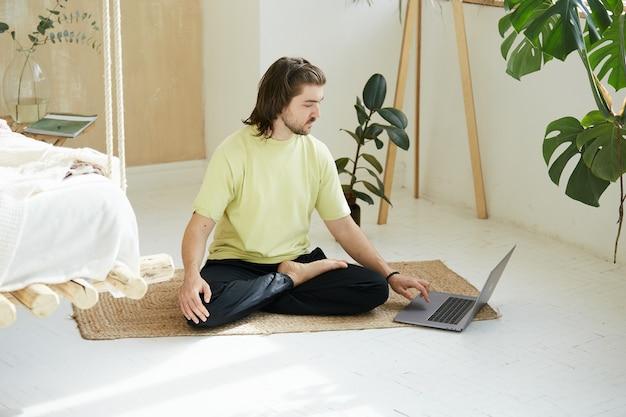 Pessoa adorável em ioga asana usando laptop, professora de ioga sentada em uma pose no chão e digitando no computador, estudando on-line de atenção plena