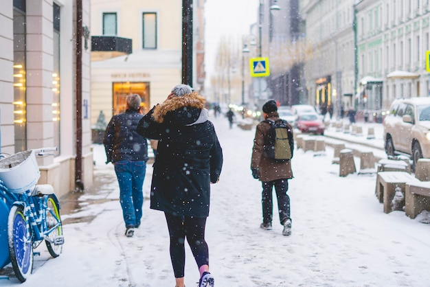 Pessoa anda nas ruas da cidade no inverno sob a neve. b