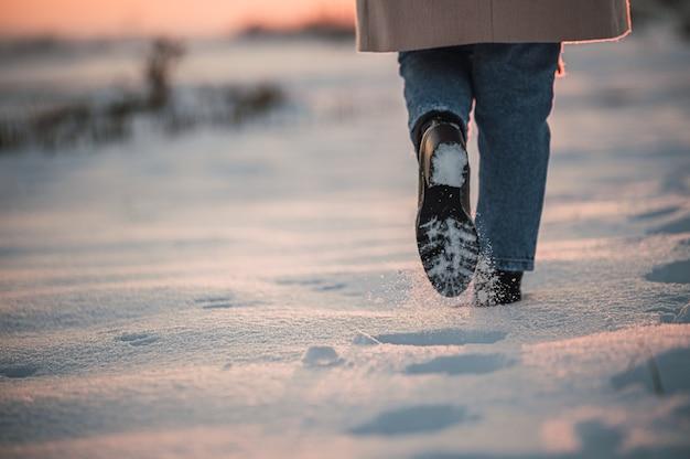 Pessoa anônima caminhando em campo nevado