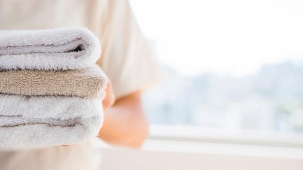 Pessoa anônima com pilha de toalhas felpudas