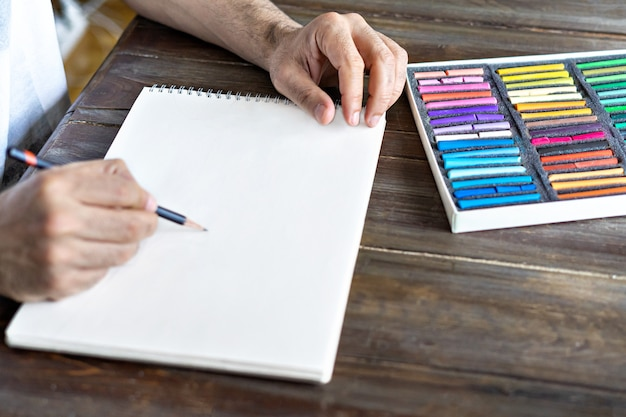 Pessoa, artista pintando com um giz de cera pastel em uma folha de papel branca com caixa com pastel