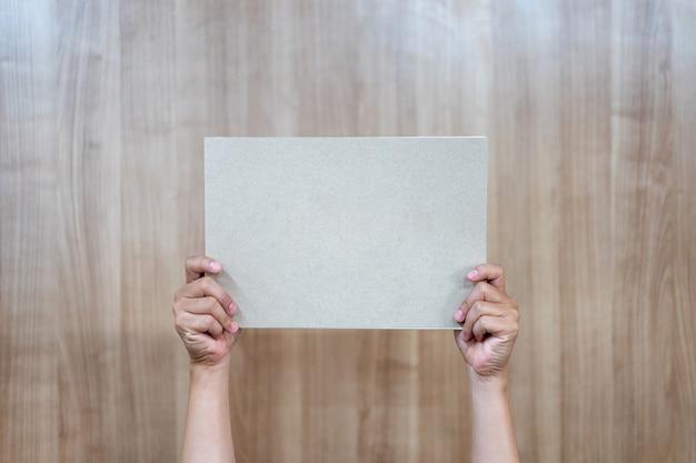 Pessoa asiática está segurando e levantando o papel a4 vazio no fundo de madeira.