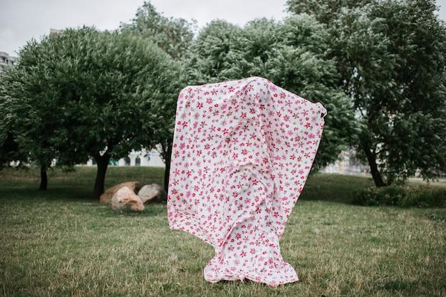 Pessoa assustadora em traje fantasma posando ao ar livre no parque outono.