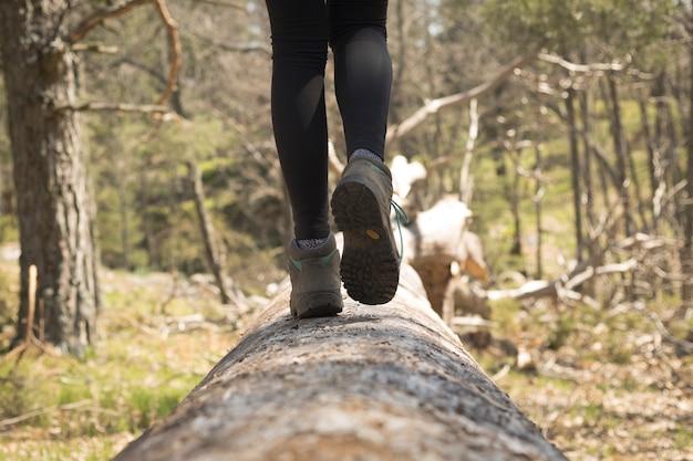 Pessoa caminhando pela floresta na natureza, close das botas