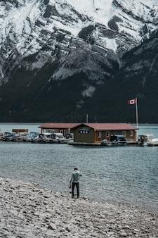 Pessoa caminhando perto da praia, vendo casas e montanhas