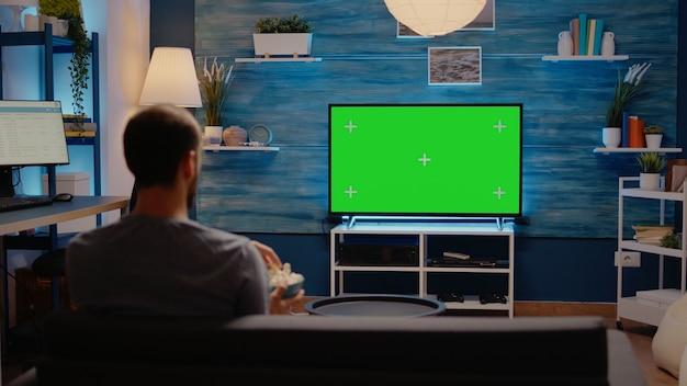 Pessoa caucasiana olhando para a tela verde da tv