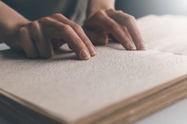 Pessoa cega lê o texto de um livro em braille