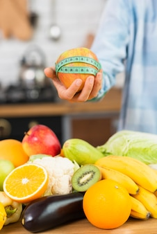Pessoa close-up, segurando a maçã e fita métrica