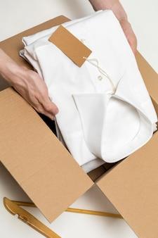 Pessoa colocando uma camisa dobrada em uma caixa