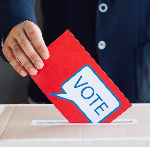 Pessoa colocando uma cédula vermelha em uma caixa de eleição