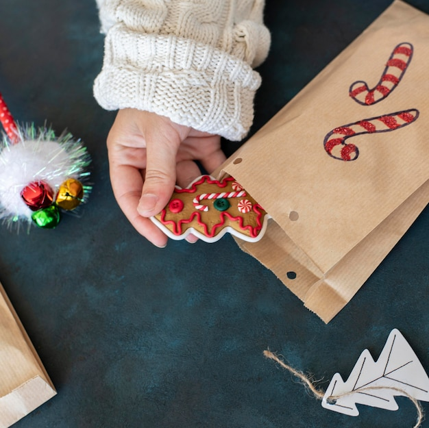 Pessoa colocando uma guloseima dentro de uma sacola de presente de natal decorada com bastão de doces