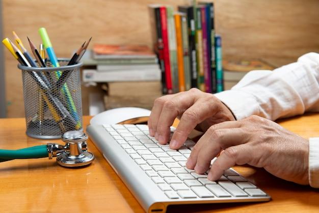 Pessoa com a mão no teclado em uma mesa de escritório