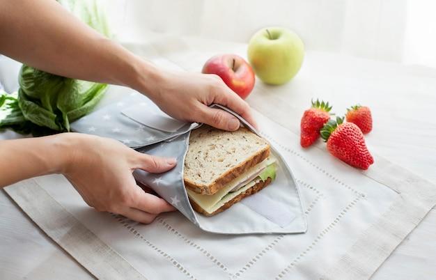 Pessoa com as mãos embrulhando sanduíche de grãos inteiros embalados em saco reutilizável conceito ecológico zero desperdício